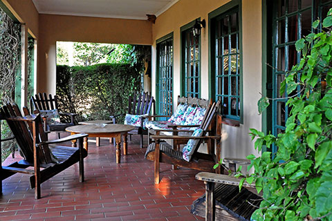 An outside look of the peaceful porch at Ekukhanyeni, with 4 chairs surrounding a table