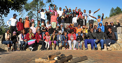 A large group of happy people standing in front of the firepit at Ekukhanyeni