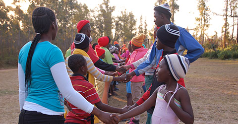 A group of people shaking hands during a programme at Ekukhanyeni