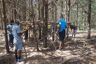 Kids working together and building a hut out of sticks at Ekukhanyeni